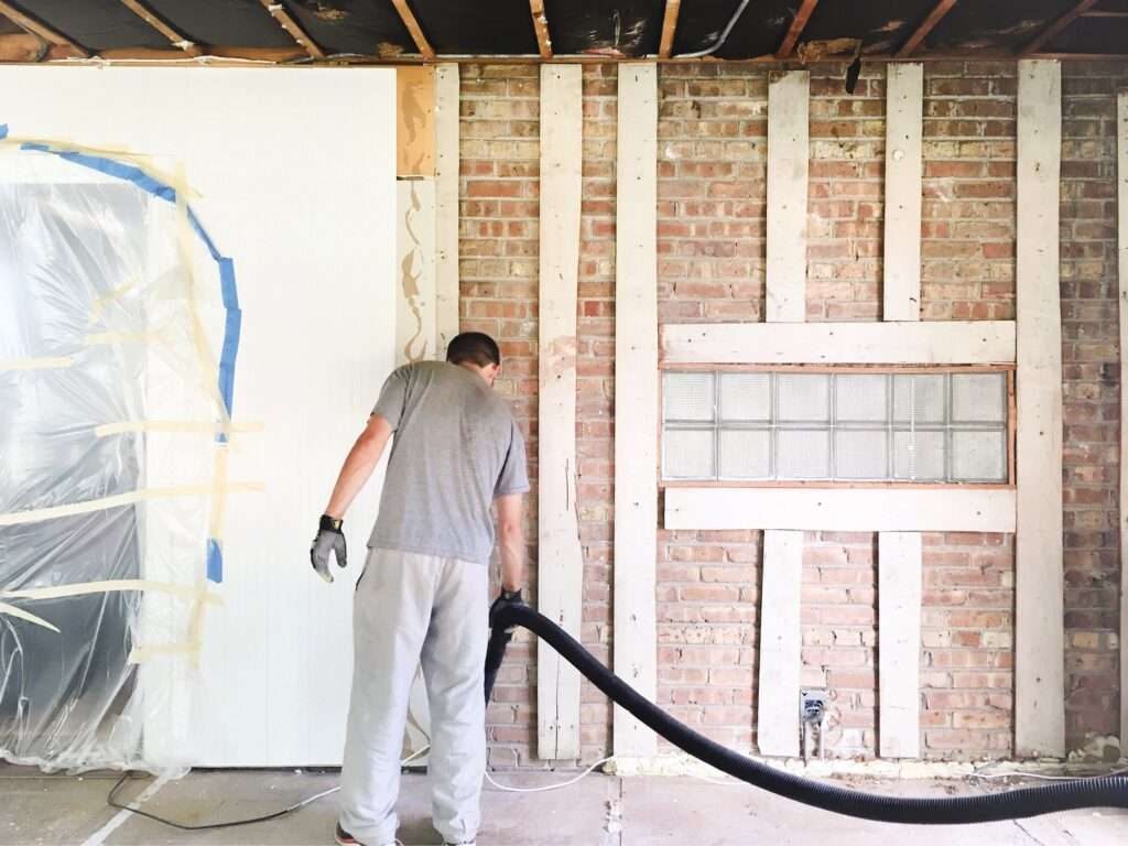 Man vacuums with long shop vac hose in renovation room addition with brick wall.